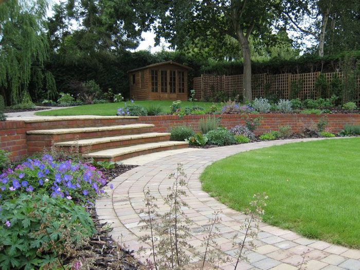 curving paths run beside a large lawn steps rise to shaded garden around the willow